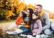 Portret młoda rodzina z dwa małymi dziećmi w jesieni naturze przy zmierzchem zdjęcia stock