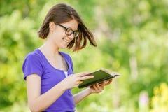 Portret młoda roześmiana kobieta czyta książkę Zdjęcia Royalty Free