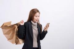 Portret młoda szczęśliwa uśmiechnięta Azjatycka kobieta z torba na zakupy i mądrze telefonem Zdjęcia Royalty Free