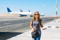 Portret młoda szczęśliwa uśmiechnięta kobieta z paszportem przy lotniskiem z trzy równinami na tle na letnim dniu Podróżować i zdjęcie stock