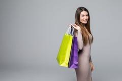 Portret młoda szczęśliwa uśmiechnięta kobieta z torba na zakupy na popielatym tle Fotografia Royalty Free