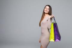 Portret młoda szczęśliwa uśmiechnięta kobieta z torba na zakupy na popielatym tle Zdjęcie Royalty Free
