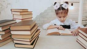 Portret młoda uczennica która siedział przy stołowym czytaniem książkę, zbiory wideo