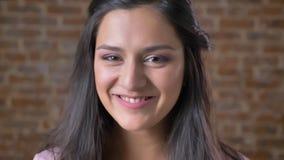 Portret młoda ufna oliwkowa dziewczyna patrzeje w kamerę i ono uśmiecha się, ściana z cegieł w tle