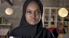 Portret młode afrykańskie muzułmańskie kobiety patrzeje w kamerze w hijab, poważny, kobiety pracuje na laptopie w nowożytnym biur zbiory