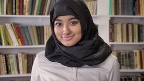 Portret młode czaruje muzułmańskie kobiety patrzeje w kamerze i ono uśmiecha się w hijab, stoi w bibliotece zdjęcie wideo