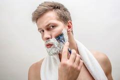 Portret młodego człowieka golenie Biel pianę na brodzie Facet jest poważny i skoncentrowany pojedynczy białe tło zdjęcia royalty free