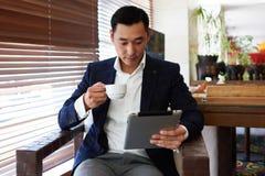 Portret młodego człowieka przedsiębiorca w formalnej odzieży cieszy się kawę podczas gdy czytający wiadomość na cyfrowej pastylce Zdjęcie Stock