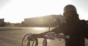 Portret młodego człowieka rowerzysta na jego motocyklu iść jechać na drodze w mieście zdjęcie wideo