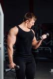 Portret młodego człowieka udźwigu mięśniowi ciężary na gym tle Zdjęcie Stock