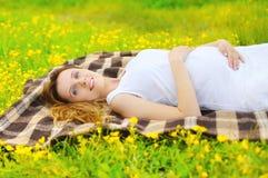 Portret młodego kobieta w ciąży odpoczynkowy lying on the beach na trawie Zdjęcia Royalty Free