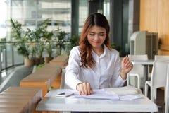 Portret młodego przyciągania Azjatycka biznesowa kobieta patrzeje jego pracę przy kawową kawiarnią w przerwa czasie Fotografia Royalty Free