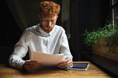 Portret młodego skoncentrowanego readhead brodaty mężczyzna, siedzi przy zdjęcie royalty free