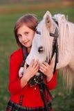 Portret młodej dziewczyny bnimaet białego konia wzorcowa głowa i patrzeć kamerę troszkę fotografia stock