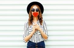 Portret młodej kobiety całowania czerwony kierowy kształtny lizak lub kryjówki jej wargi w czarnym round kapeluszu, biała pasiast fotografia royalty free