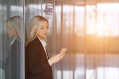 Portret młodej kobiety dosłania wiadomość na smartphone w biurze kosmos kopii Fotografia Royalty Free