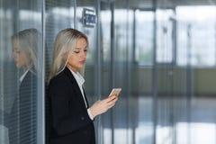 Portret młodej kobiety dosłania wiadomość na smartphone w biurze kosmos kopii Obrazy Royalty Free