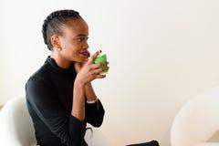 Portret młodej kobiety obsiadanie w białym krześle z kawą i telefonem komórkowym zdjęcie stock