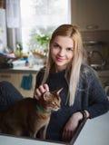 Portret młodej uśmiechniętej uroczej blondynki europejska kobieta cieszy się moment migdali abyssinian kota pozuje przeciw zamaza obraz stock