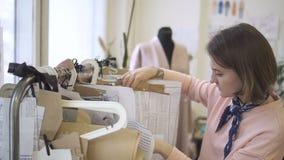 Portret młody żeński projektant który wybiera krzywy dla sukni w jej jaskrawym studiu, zbiory