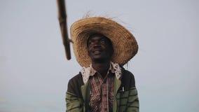 Portret młody afrykański mężczyzna obsiadanie w słomianym kapeluszu w łodzi i opowiadać, pokazuje ręką zbiory wideo