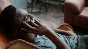 Portret młody Afrykański mężczyzna siedzi w krześle Męski używa Smartphone, opowiadający, uśmiechnięty i roześmiany Fotografia Stock