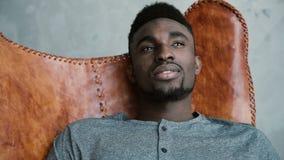 Portret młody Afrykański męski obsiadanie w rzemiennym krześle, myśleć o coś i ono uśmiecha się Mężczyzna patrzeje zamyślenie Zdjęcie Stock