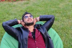 Portret Młody Arabski Męski mężczyzna, uczeń Kłama na krześle, Smilin Zdjęcia Stock