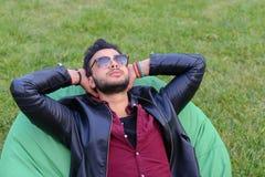 Portret Młody Arabski Męski mężczyzna, uczeń Kłama na krześle, Smilin Zdjęcia Royalty Free