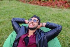 Portret Młody Arabski Męski mężczyzna, uczeń Kłama na krześle, Smilin Obrazy Royalty Free