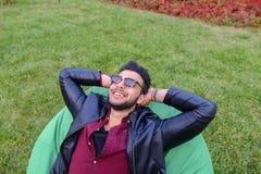 Portret Młody Arabski Męski mężczyzna, uczeń Kłama na krześle, Smilin Obrazy Stock