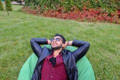 Portret Młody Arabski Męski mężczyzna, uczeń Kłama na krześle, Smilin Fotografia Royalty Free