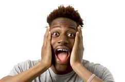 Portret młody atrakcyjny afro amerykański mężczyzna zaskakujący z rozpieczętowanym usta i szeroko otwarty oczami Obrazy Royalty Free