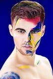 Portret młody atrakcyjny mężczyzna z barwioną twarzy farbą na błękitnym tle Fachowa Makeup moda ffantasy sztuka Fotografia Stock
