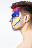 Portret młody atrakcyjny mężczyzna z barwioną twarzy farbą na białym tle Fachowa Makeup moda ffantasy sztuka Zdjęcie Royalty Free