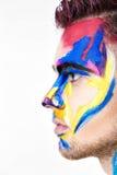 Portret młody atrakcyjny mężczyzna z barwioną twarzy farbą na białym tle Fachowa Makeup moda ffantasy sztuka Obraz Stock