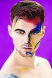 Portret młody atrakcyjny mężczyzna z barwioną twarzy farbą na purpurowym tle Fachowa Makeup moda ffantasy sztuka Zdjęcie Royalty Free