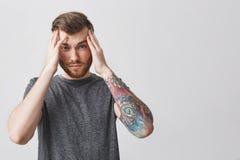 Portret młody atrakcyjny nieszczęśliwy caucasian facet z elegancką fryzurą w przypadkowym szarym koszulki mienia czole z obraz stock