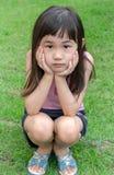 Portret Młody Azjatycki dziewczyny przycupnięcie na trawie fotografia royalty free