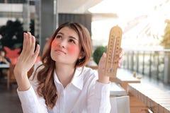 Portret młody Azjatycki kobiety mienia termometr i uczucie w ten sposób gorący z wysokotemperaturowym na biurku przeciw światło s fotografia royalty free