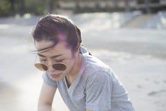Portret młody azjatykci kobiety obsiadanie przy plażą tła zegarowy pojęcie odizolowywający czas wakacje ściany biel zamazujący tł Zdjęcia Royalty Free