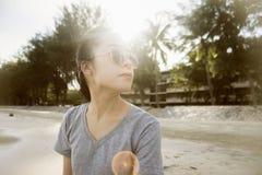 Portret młody azjatykci kobiety obsiadanie przy plażą tła zegarowy pojęcie odizolowywający czas wakacje ściany biel zamazujący tł Zdjęcie Royalty Free