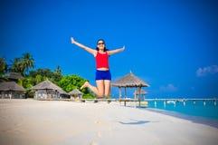 Portret młody azjatykci przyglądający kobiety skakać szczęśliwy przy piękną tropikalną plażą przy Maldives Fotografia Royalty Free