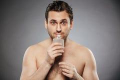 Portret młody bez koszuli mężczyzna wącha aftershave Obraz Royalty Free