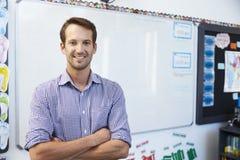 Portret młody biały męski nauczyciel w szkolnej sala lekcyjnej