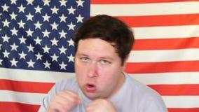 Portret młody biały patrioty mężczyzna pozuje z walczącymi pięściami na tle usa flaga zdjęcie wideo