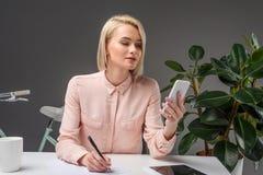 portret młody bizneswoman używa smartphone przy miejscem pracy zdjęcie royalty free