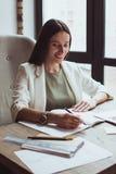 Portret młody bizneswomanu obsiadanie z jej laptopem w biurze fotografia stock