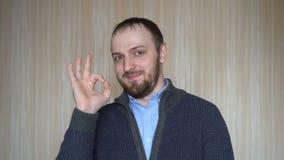 Portret młody brodaty mężczyzna gestykuluje ok szyldowego, indoors zbiory wideo