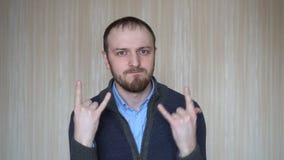 Portret młody brodaty mężczyzna gestykuluje rock and roll znaka, indoors zbiory